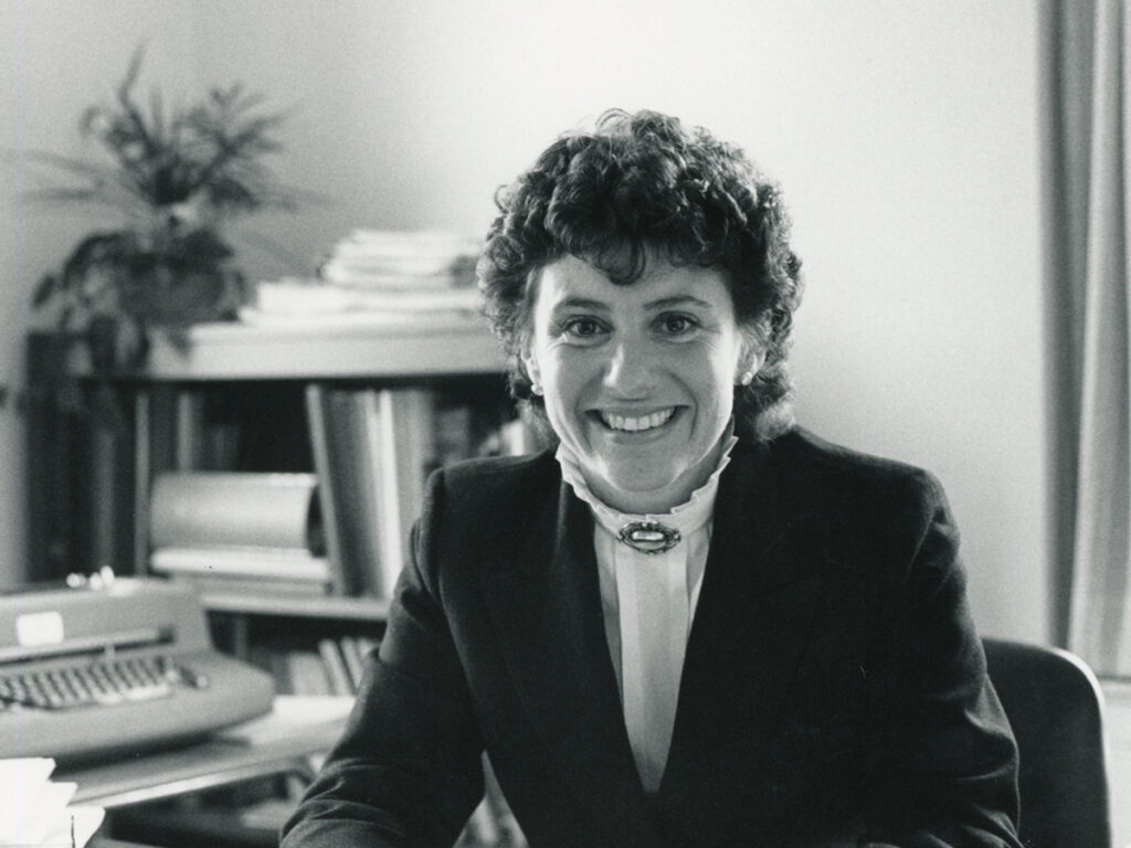 black and white photo of Jane Brown seated at desk with bookcase and electric typewriter behind her.