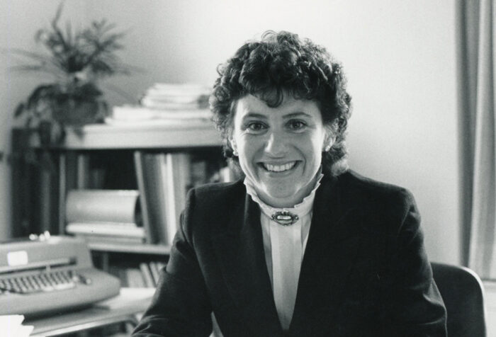 jane brown seated at desk with bookcase and typewriter behind her