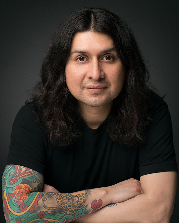 michael cavazos in black t-shirt, arms crossed