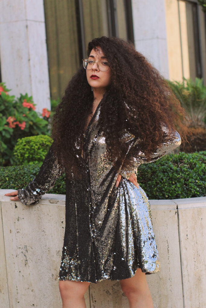 paloma valenzuela in black sequined dress leaning agains planter
