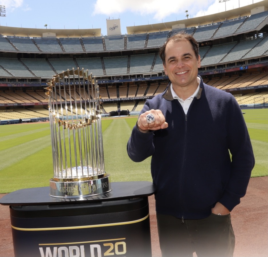 man stands in Dodger Stadium next to trophy on pedestal, extending fist to show large ring