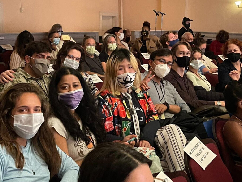 men and women wearing face masks, sitting in audience, looking at camera