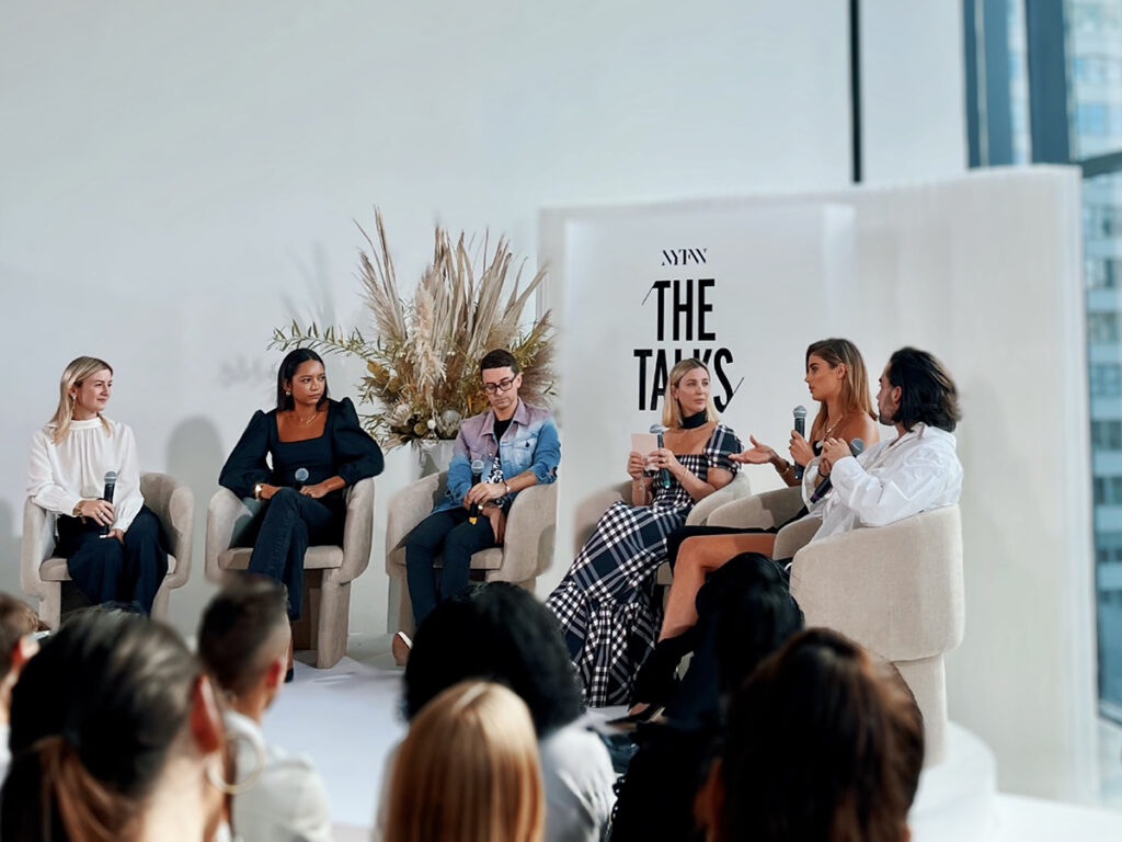 An audience watches panelists speak in white room
